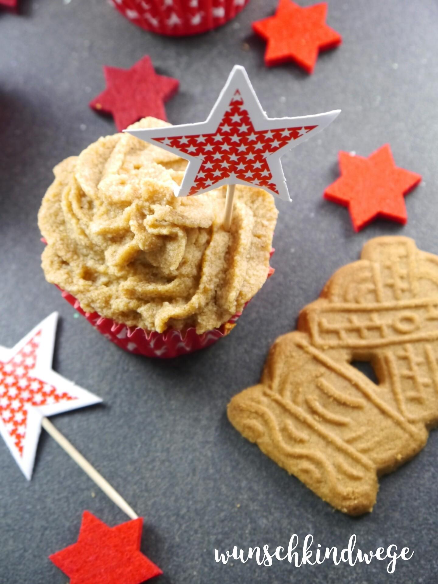 Das Bild zeigt Bratapfelcupcakes mit Spekulatiussahne auf schwarzem Hintergrund. Es liegen rote Sterne sowie Spekulatius daneben.