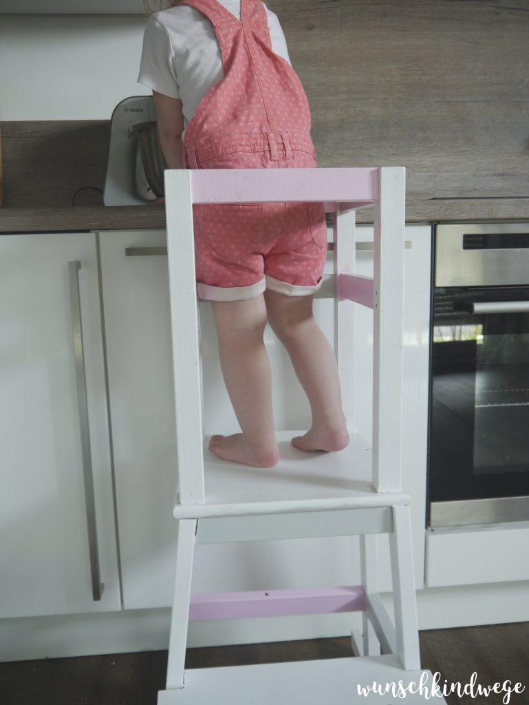 Kleinkind steht auf Learning Tower